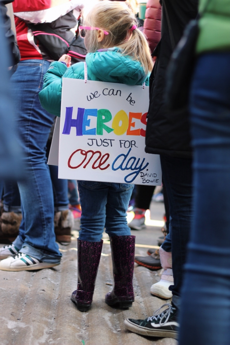"Picture of a small girl wearing a sign that says ""We can be heroes just for one day,"" a quote from David Bowie"